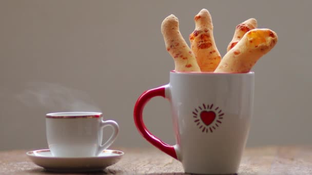 cheese bread in the form of chopsticks with a cup of coffee