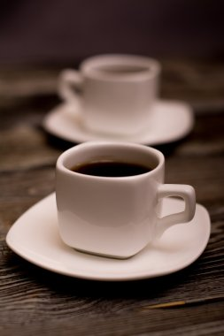 two small white cups of coffee on wooden background