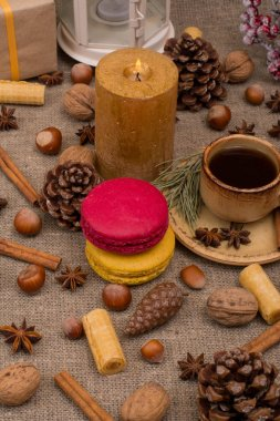 Cup of coffee, macaroons, cookies, walnuts, hazelnuts, cinnamon sticks, star anise, cone, candle, fir branch on sackcloth fabric