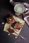 Fotografie Homemade brownie with pistachios served with dark beer on stone table