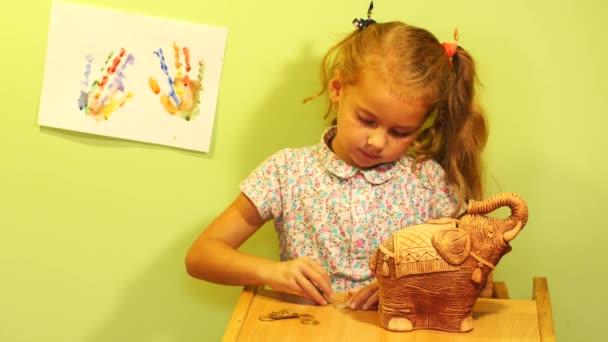 Malá holčička šetří peníze (mince). Dívka vkládat mince peníze box. Roztomilá dívka s Pokladnička