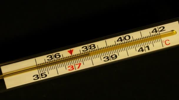 Temperaturanstieg auf einem Thermometer. Quecksilberthermometer aus Glas zeigt hohe Körpertemperatur an. Temperaturanstieg und -abfall auf dem Thermometer. schwarzer Hintergrund. Nahaufnahme