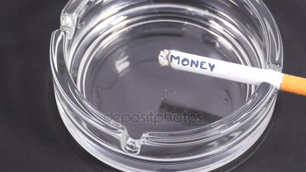 Szó pénz írott-ra a cigaretta. Égési szó pénzt írás egy cigaretta egy hamutartó.
