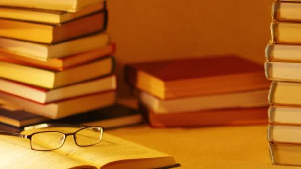 Na hromadě knih se zobrazí slovní spojení nejlepší knihy. Otevřená kniha s brýlemi na pozadí knihy. Zastavení pohybu
