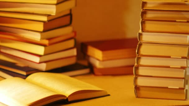 The phrase READ ME described with letters on stack of books. A pile of books with the words read me appears on the table near the open book with glasses. Stop motion