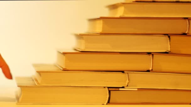 The movement of the hand up the makeshift stairs of books. Hand walks up the steps of books.