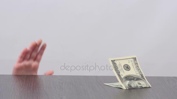 Kind die hand unter dem Tisch zeigen und stiehlt Banknote. Hand von kleinen Mädchen auf dem Tisch einen Dollarschein tastend und nimmt es. Kind stiehlt Geld