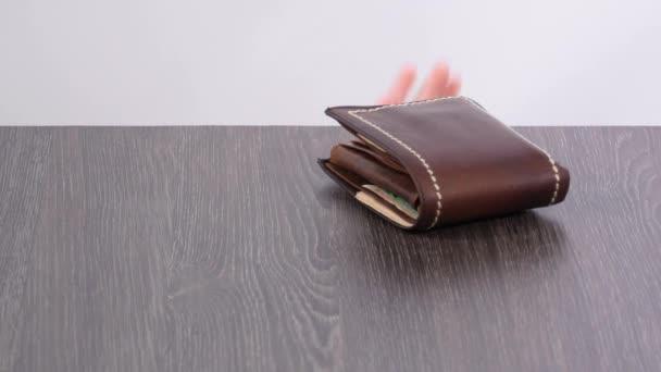 Kabelka na stole, dětská ruka krade peněženku.