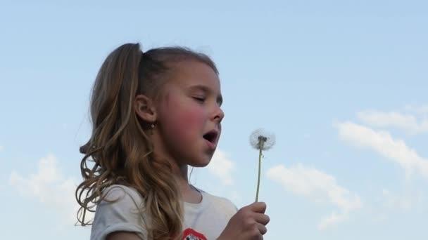 Schöne Mädchen bläst Löwenzahn Himmelshintergrund wiederholt. Teenager-Mädchen auf der Suche in die Kamera dreht sich zur Seite und bläst einen Löwenzahn. Slow-motion