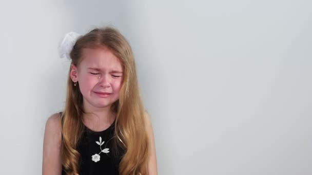 Beautiful crying little girl on white background. Blonde young girl cries compassionately. Slow motion– stock footage