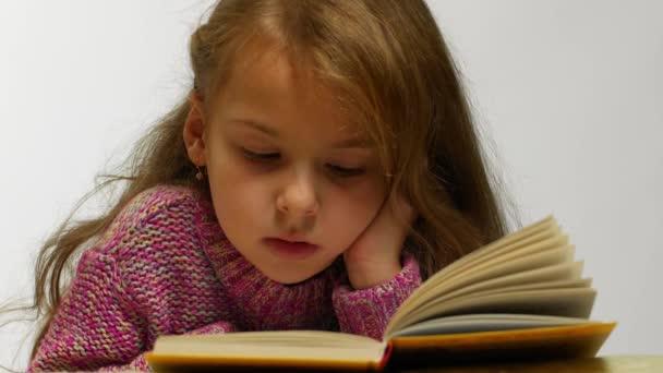 Mladá dívka s úsměvem při čtení knihy. Čelní pohled roztomilé dospívající ležel s otevřenou knihu