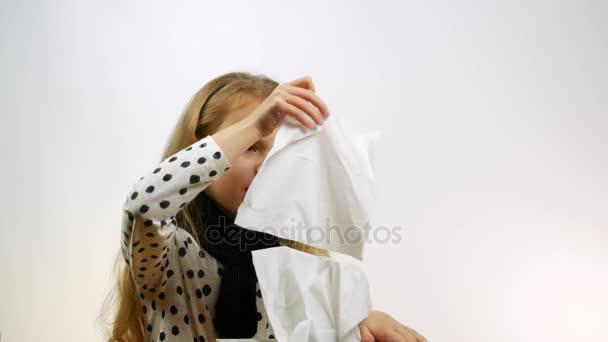 Kranke kaukasische Mädchen blasen Nase in Gewebe. Nettes Kind, das an Rhinitis leidet, bläst sich die Nase, ein Studio-Schuss.