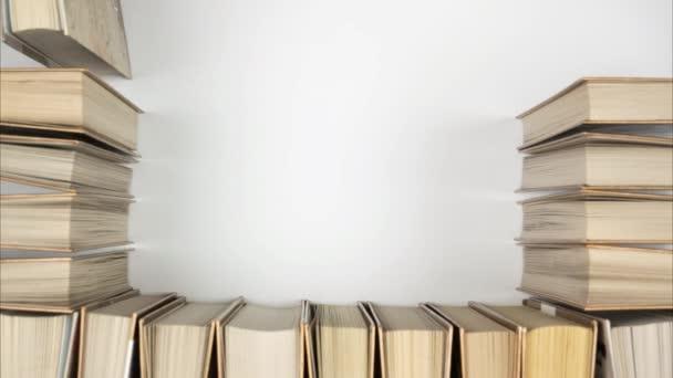 Buchrahmen, Stop-Motion. Bücher von oben, die einen Rahmen für Text in der Mitte bilden.