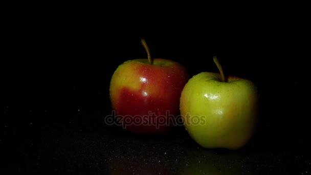 Dvě jablka na tmavém pozadí. Kapka vody teče dolů apple.