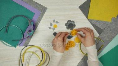 Craftswoman pracovní stůl. Kus plsti a ručně vyráběné květy na pracovním stole. Pohled shora