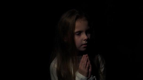 das Kind betet im Dunkeln