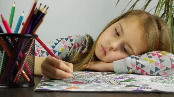 Tvář smutná dívka kreslení pastelkami. Unavené dítě odpočívá zbarvení proti stresu kniha.