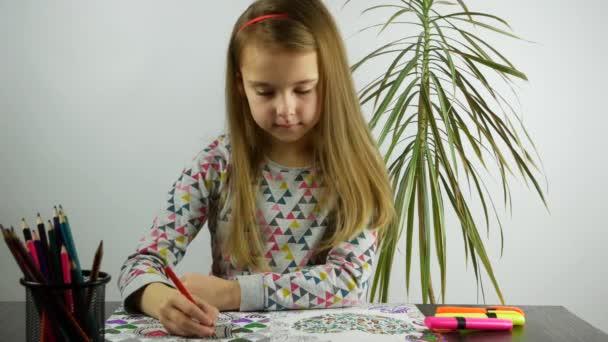 Dívka u stolu zbarvení poznámkového bloku.
