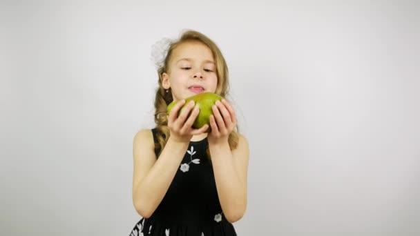 Blond dívka v krásných šatech jíst hruška na bílém pozadí.