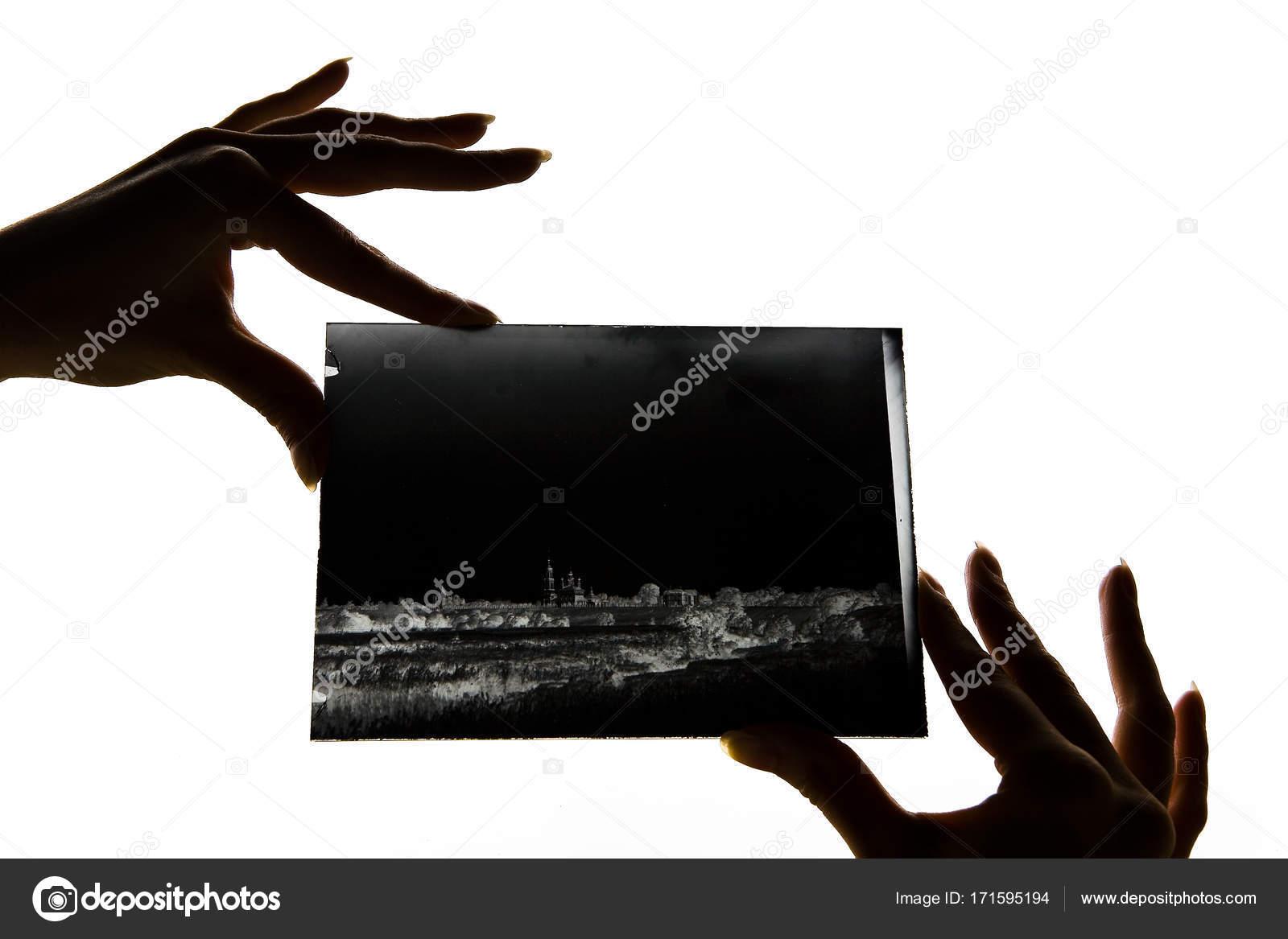 Beautiful female fingers hold a glass negative  — Stock