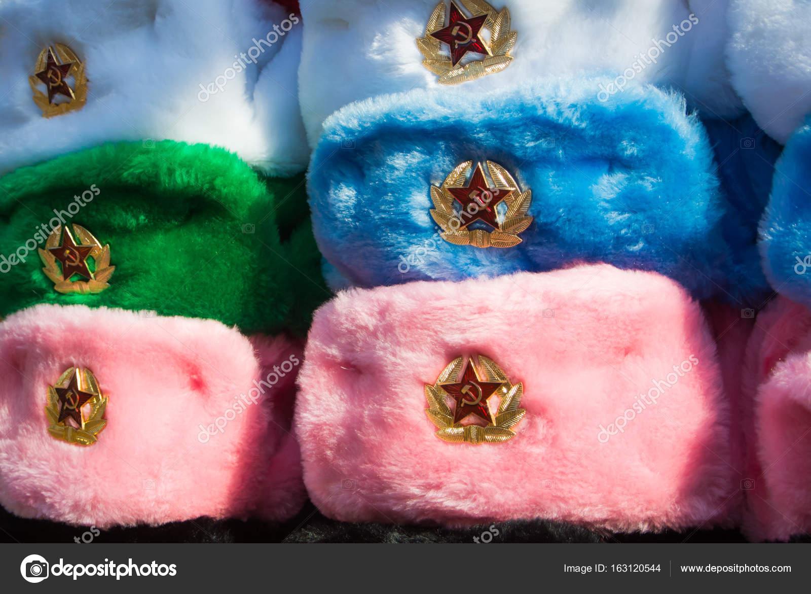 a97dc0d694e Řádky z Ruské zimní čepice různých barev s armádou emblémy na tržišti v Old  Arbat street
