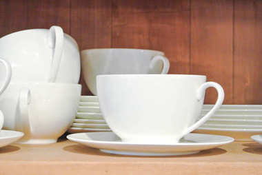 Bright white dishes, plates and cups standing on brown wooden sh