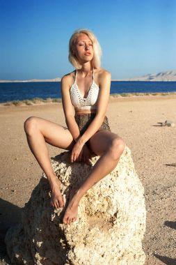 Caucasian girl sunbathing on the beach