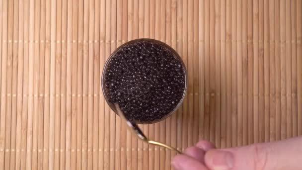 Schale mit schwarzem Kaviar. Löffel schwarzer Kaviar gewinnt
