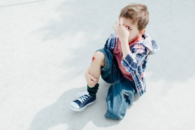 Crying injured boy with a bleeding knee