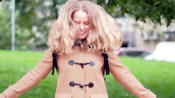 Fiatal szőke lány fejhallgató boldogan Jumping a trambulin, egy parkban, a göndör haját, repülő lassított bézs bundában