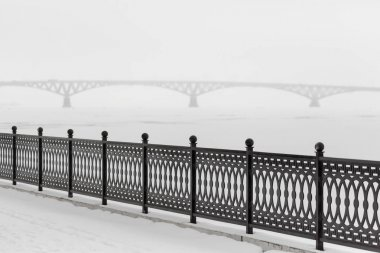 The metal fence on the waterfront in the city of Saratov, Russia. In the background is the road bridge across the Volga River. Winter cloudy day. Ice on the river.