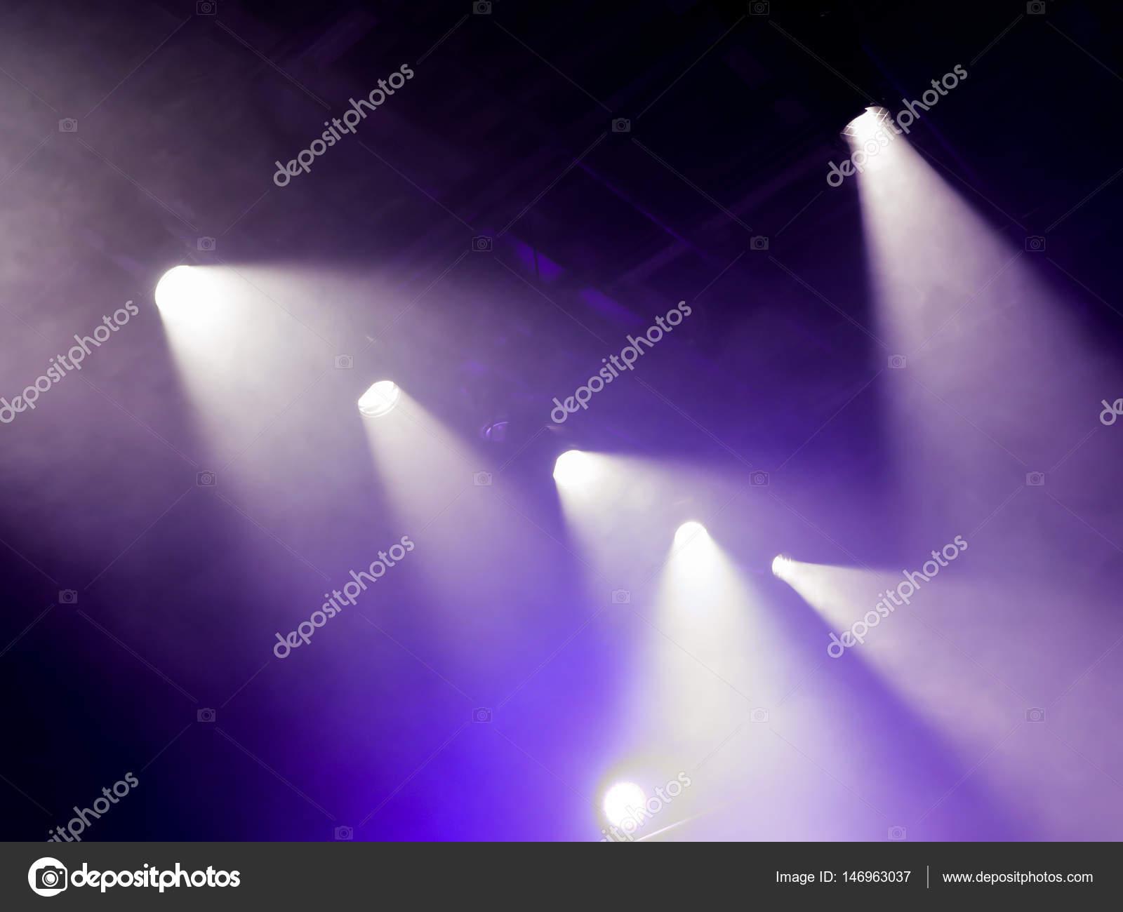 I raggi di luce da sotto i riflettori attraverso il fumo