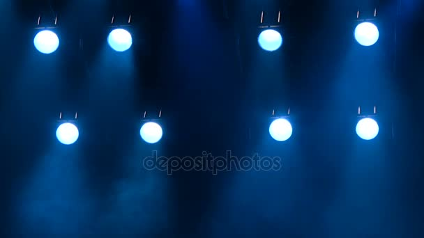 La luce blu da faretti attraverso il fumo sul palco durante una