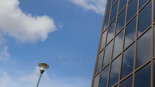 Plovoucí v obloze mraky odrážejí v oknech budovy. Pouliční lampa. Čas-chyba nahrávání