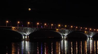 Full moon rises over the bridge. Road bridge between the cities of Saratov and Engels, Russia. The Volga River. The evening lights of cars and street lights