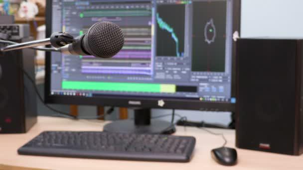 Mikrofon a háttérben, a számítógép-monitor. Otthoni felvétel Studio. Közelről. A hangsúly az előtérben. Elmosódott háttér. Szoftver hangok rögzítésére és szerkesztésére. 4k, Uhd, Ultra Hd