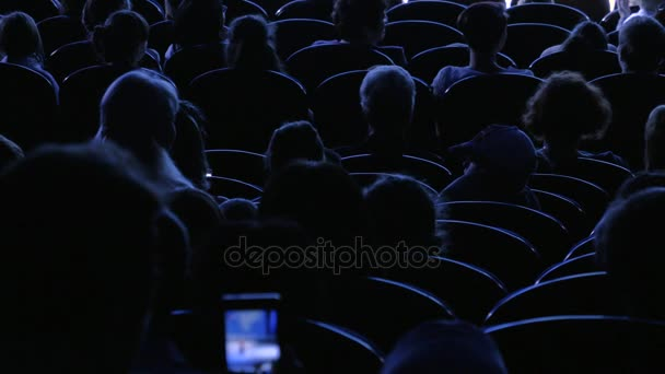 The audience applauded for a performance or presentation in the theater. Video from the back. Children and adults alike. Clip footage in 4K