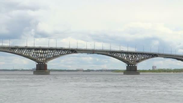Tři paluby motorové lodě prochází pod silniční most přes řeku Volhu. Čas-chyba nahrávání. Letní den. Rusko, město Saratovské. Klip záběrů v rozlišení 4k.