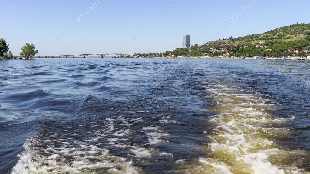 Photographing from the stern of the ship. Summer river landscape. The Volga river in Saratov, Russia. Road bridge between the cities of Saratov and Engels