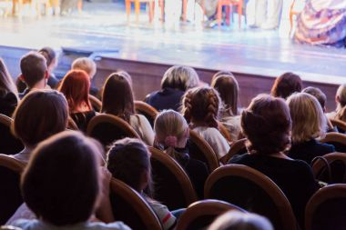 The audience in the theater watching a play. The audience in the hall: adults and children