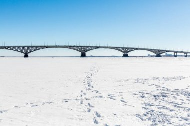 Road bridge across the Volga river between the cities of Saratov and Engels. Winter day. Ice on the river