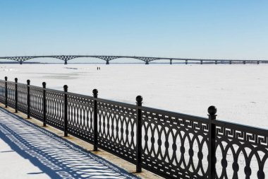 The metal fence on the waterfront. Winter day. Road bridge between the cities of Saratov and Engels. The Volga River, Russia stock vector