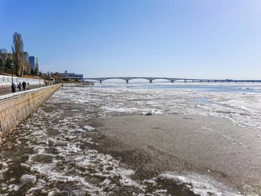 Road bridge over the Volga river between Saratov and Engels, Russia. Ice drift on the river in spring. Embankment in the city of Saratov. Sunny day in April. stock vector