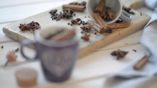 Šálky s anýz, skořice, hřebíček a pepř na dřevěný starý stůl
