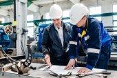 Mladý úspěšný inženýr popisuje důležité technické změny v designu s kolegou práce