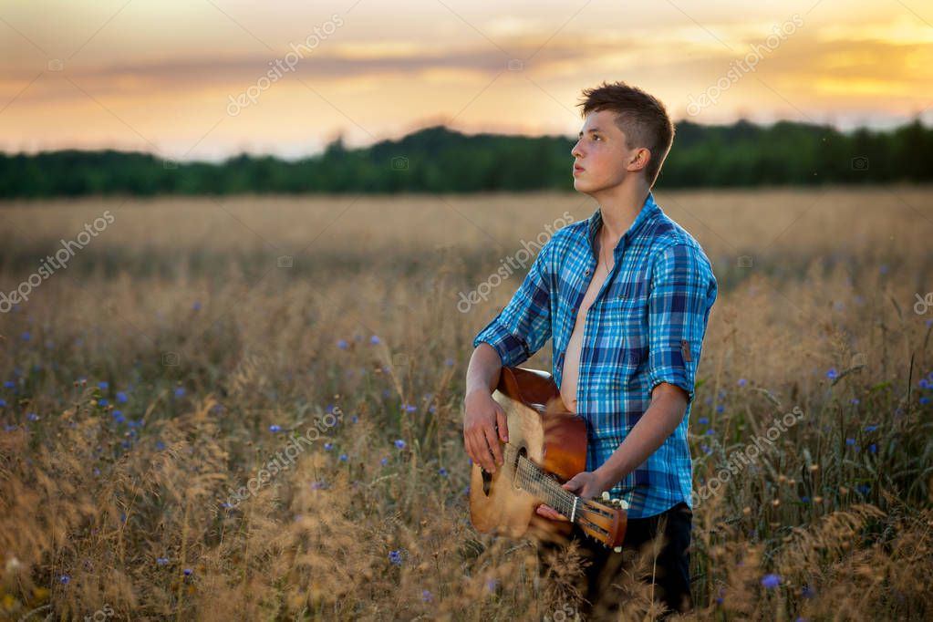Romantic young man stands in a field with a guitar at sunset