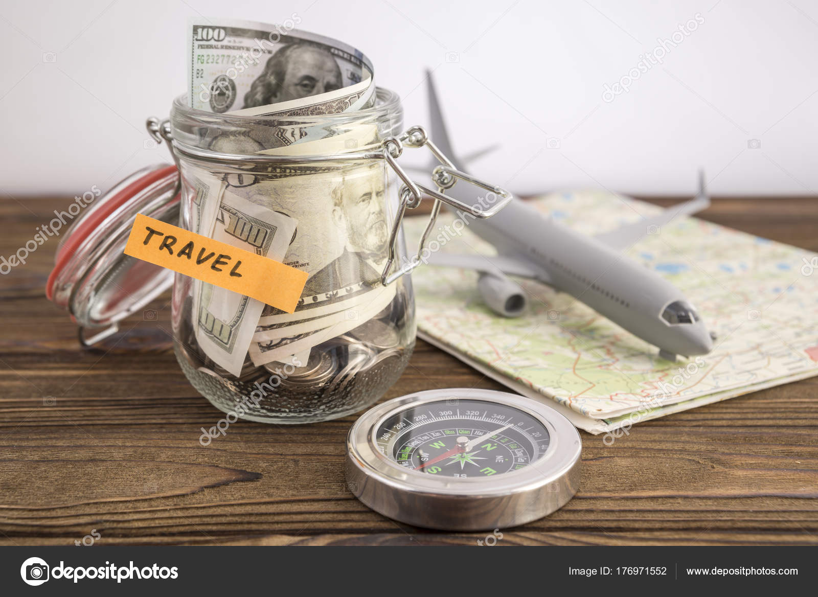 Budget travel concept travel money savings glass jar toy aircraft travel money savings in a glass jar with toy aircraft on world map and compass to save for the trip photo by gerasimovfoto174 gumiabroncs Gallery