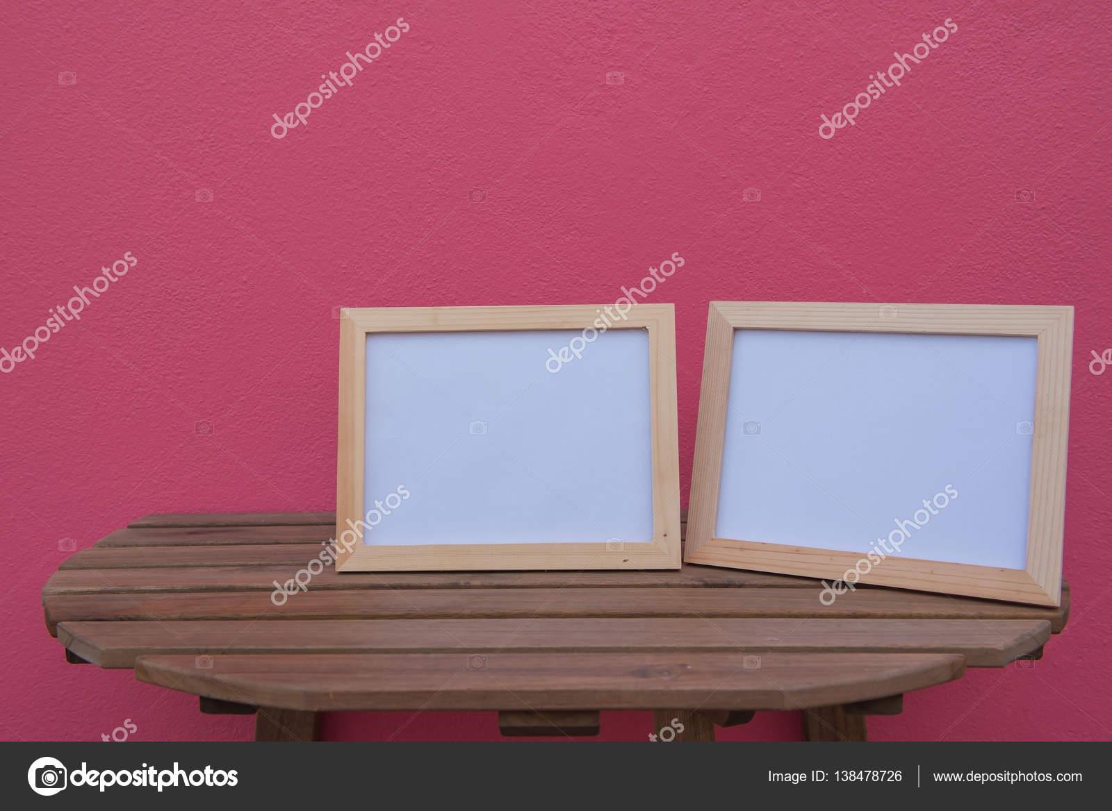 Zwei Fotorahmen auf einem hölzernen auf rosa Hintergrund — Stockfoto ...
