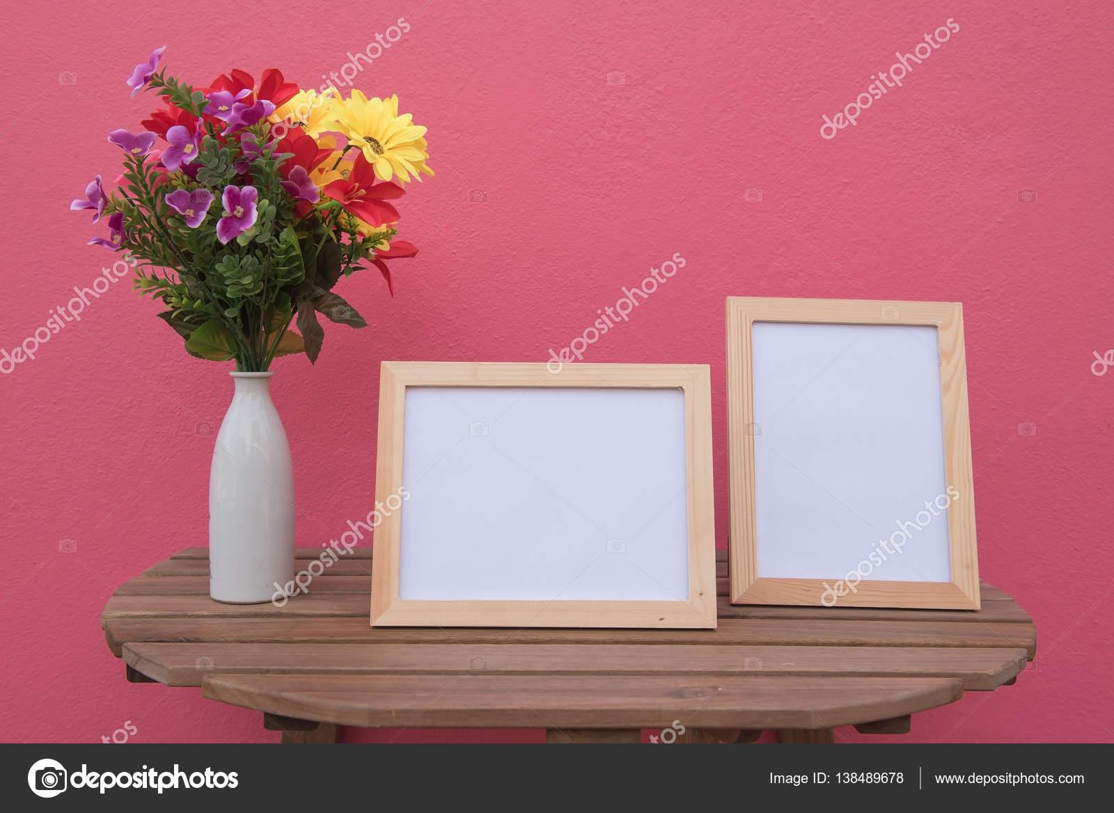 Zwei Fotorahmen aus Holz und Blumen in Glas auf rosa Hintergrund ...