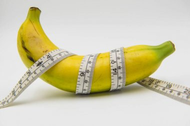 Yellow banana and Measuring tape wrapped around on white background